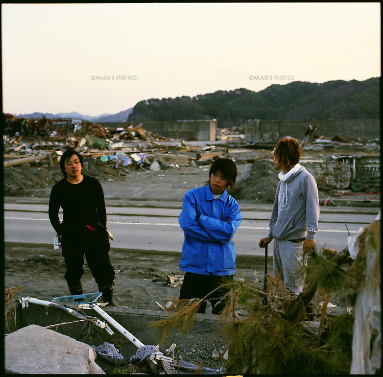 """On March 11, 2011, the earthquake of magnitude 9.0, the biggest earthquake in the history of Japan and the fourth biggest earthquake in the world after year 1900, shocked the Tohoku area of Japan. In about 30 minutes, devastating tsunami reached, affecting the coastline with a length of 500 km (310 miles). The tsunami wave height of 39 meters (128 feet) was recorded in a port town in Tohoku. The tsunami swallowed villages along the coast and washed away all houses. The earthquake and tsunami killed more than 15,800 people, and still more than 3,500 people are missing. <br /> From left, Mitsuteru Kurasawa, 20, Kota Suzuki, 17, and Haruma Miura, 20, in their devastated town, Otsuchi, Iwate, in one month after the earthquake and tsunami. Mr. Kurasawa was fishing at port, Mr. Suzuki was in a driving school, and Mr. Miura was trying to let sleep his baby when the earthquake hit thier town. All of them evacuated right away, fearing for tsunami. """"We are so accustomed to tsunami warning that many of us did not believe,"""" said Mr. Miura. The tsunami swallowed up the whole town of Otsuchi and left 802 people dead and 520 people missing. The mayor was also killed in the tsunami. """"Right now, we were roaming around the town to see something is left,"""" Mr. Kurasawa said. """"But, there is nothing. We cannot even remember what was there. We have to start from Zero."""""""