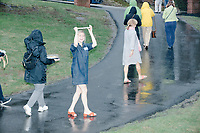 People leave in the rain after Democratic presidential candidate and South Bend mayor Pete Buttigieg spoke at a house party with the Bedford Democrats in Bedford, New Hampshire, on Sat., Apr. 20, 2019. The candidate stood on a chair throughout his speech.