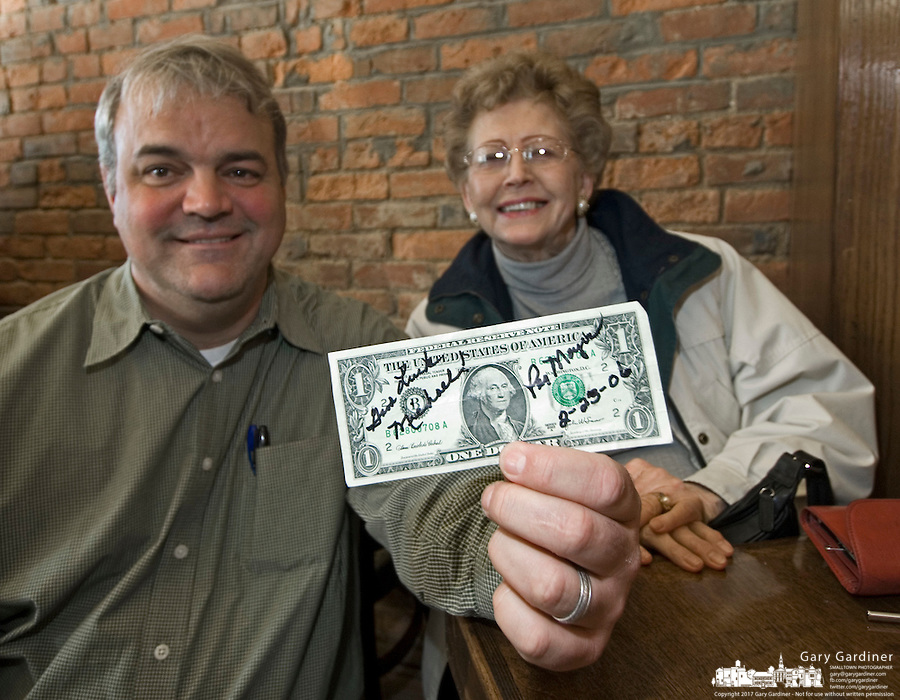 Owner Mike Purdum, left, holds the first dollar  earned at the Old Bag of Nails restaurant after it was signed by Peggy Moyer, 79, right, his first customer. Moyer drank one of the the first beers sold at the restaurant and bar in downtown Westerville, Ohio, Thursday, February 23, 2006. The business occupies a building at the main crossroads in the city that was home to the Anti-Saloon League.