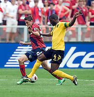 Alejandro Bedoya (22) of the USMNT fights for the ball with Shavar Thomas (4) of Jamaica during the game at RFK Stadium in Washington, DC.  The USMNT defeated Jamaica, 2-0.