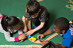 Preschool 4 year olds two boys and a girl playing together with train set