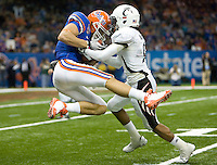01 January 2010:  Dominique Battle of Cincinnati tackles Riley Cooper of Florida after Cooper catches a long pass from Tim Tebow during the game during Sugar Bowl at the SuperDome in New Orleans, Louisiana.  Florida defeated Cincinnati, 51-24.