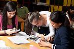 Education high school female teacher helping girl with mathmatics problem nearby student using calculator