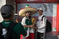 WARSAW, POLAND - June 12, 2018: A Mexico soccer fan holds a FIFA World Cup trophy while posing for a photograph with another fan at Warsaw Chopin Airport.