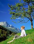 DEU, Deutschland, Bayern, Oberbayern, Berchtesgadener Land:  Frau sitzt unterm Baum in einer Wiese vorm Untersberg | DEU, Germany, Bavaria, Upper Bavaria, Berchtesgadener Land: woman sitting under a tree in a meadow and Untersberg mountain