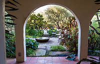 Secret garden Moorish influenced courtyard room seen through arch over tile walkway; McAvoy Garden - California; Design - Ground Studio