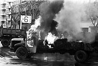 Carrefour boulevard Lazare-Carnot et allées François-Verdier, devant le Monuments aux Combattants. 6 février 1978. Vue d'ensemble d'un camion en feu (vue de profil), flammes, fumée ; en arrière-plan autre camion benne. Cliché pris lors d'une manifestation organisée par une trentaine de transporteurs et artisans locaux pour protester contre le chantier de l'autoroute A61 donné à une grosse société du centre de la France. Manifestation patronée par la Confédération Intersyndicale de Défense et d'Union Nationale des Travailleurs Indépendants (CIDUNATI).