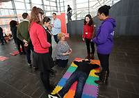Suzy Davies AM is being shown how to give first aid by young people of the Cardiff Youth Council