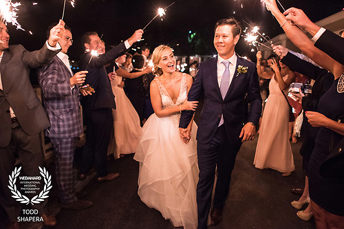 At the American Yacht Club, a happy couple enjoys a sparkler exit from their wedding ceremony.