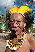 Aldeia Baú, Para State, Brazil. Old Kayapo chief Mantinol wearing a tooth necklace, beads and feather cocaa headdress and botoque lip plate - and glasses.