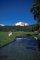 Mother and daughter walking alongside Kings Creek with Mt. Lassen in background,  California