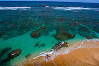Young woman surfer enters crystal clear waters of Hideaways Beach, a snorkeling heaven in Princeville, North Shore of Kauai