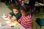 Education Elementary school Grade 1 mathematics hands on learning boy and girl counting and comparing rows of colored squares and rows of connected colored cubes horizontal
