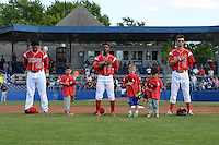 "Batavia Muckdogs players Carlos Duran (25), Mason Davis (7) and Aaron Blanton (11) stand for the national anthem with young fans as part of the ""Stars of the Game"" program before a game against the State College Spikes on June 22, 2014 at Dwyer Stadium in Batavia, New York.  State College defeated Batavia 10-3.  (Mike Janes/Four Seam Images)"