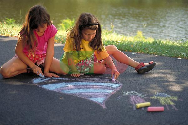 young girls drawing on sidewalk