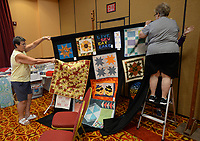 Sheila Bayles (left) of Rogers and Adele Atha of Fayetteville, both members of the Quilters United in Learning Together Guild, set up a panel of quilts to be auctioned Friday, Oct. 8, 2021, while setting up for a quilt show and sale set for 9 a.m. to 3;30 p.m. today at the Rogers Convention Center. The organization has members throughout Northwest Arkansas and will use money generated by the event to fund its outreach and education efforts. Visit nwaonline.com/211009Daily/ for today's photo gallery.<br /> (NWA Democrat-Gazette/Andy Shupe)