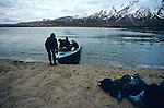 Early in the morning, hikers use a boat to cross a lake in the Tajikistan Pamir mountains.