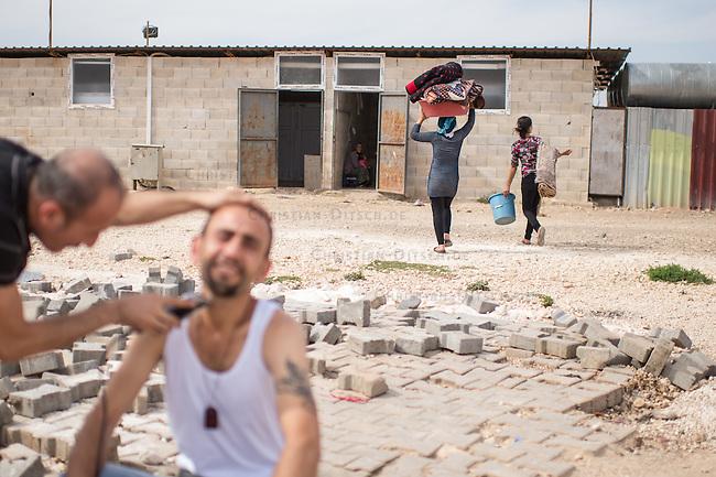 Fluechtlingscamp Arin Mirxan nahe der Ortschaft Suruc im tuerkischen Grenzgebiet zu Syrien. Hier leben ca. 250 Menschen, die vor dem Krieg des IS gegen die Kurden in dem Kurdengebiet Rojava von Syrien aus in die Tuerkei geflohen sind.<br /> Im Bild: Zwei Frauen bringen Waesche zum waschen. Im Vordergrund rasiert ein Fluechtling einen Freund.<br /> 12.10.2015, Suruc/Tuerkei<br /> Copyright: Christian-Ditsch.de<br /> [Inhaltsveraendernde Manipulation des Fotos nur nach ausdruecklicher Genehmigung des Fotografen. Vereinbarungen ueber Abtretung von Persoenlichkeitsrechten/Model Release der abgebildeten Person/Personen liegen nicht vor. NO MODEL RELEASE! Nur fuer Redaktionelle Zwecke. Don't publish without copyright Christian-Ditsch.de, Veroeffentlichung nur mit Fotografennennung, sowie gegen Honorar, MwSt. und Beleg. Konto: I N G - D i B a, IBAN DE58500105175400192269, BIC INGDDEFFXXX, Kontakt: post@christian-ditsch.de<br /> Bei der Bearbeitung der Dateiinformationen darf die Urheberkennzeichnung in den EXIF- und  IPTC-Daten nicht entfernt werden, diese sind in digitalen Medien nach §95c UrhG rechtlich geschuetzt. Der Urhebervermerk wird gemaess §13 UrhG verlangt.]