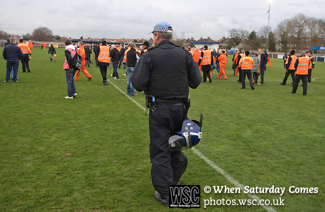 Wealdstone 0 Newport County 0, 17/03/2012. St Georges Stadium, FA Trophy Semi Final. A lone riot police officer on the pitch at St Georges Stadium, home ground of Wealdstone FC, as the club played host to Newport County (yellow) in the semi-final second leg of the F.A. Trophy. The game ended in a goalless draw, watched by a capacity crowd of 2,092 which meant the visitors from Wales progressed by three goals to one to the competition's final at Wembley, where they would meet York City. The F.A. Trophy was the premier cup competition for non-League clubs in England and Wales affiliated to the Football Association. Photo by Colin McPherson.
