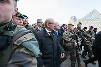 French Defence Minister Jean-Yves Le Drian (L) and Interior Minister Bruno Le Roux speak to French soldiers at the Louvre Museum as emergency security measures continue ahead of New Year's eve celebrations in and around the French capital, in Paris, France, December 30, 2016.
