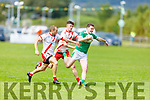 John Mitchels Niall Sheehy been tackled by Colm Ó Muircheartaigh and PJ Mac Láimh of An Ghaeltacht in the Intermediate Football Championship.