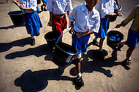 Kindergarten students at Kartini Emergency School carry water buckets from a pump during a lesson in clothes washing. Since the early 1990s, twin sisters Sri Rosyati (known as Rossy) and Sri Irianingsih (known as Rian) have used their family inheritance to set up and run 64 schools in different parts of Indonesia, providing primary education combined with practical skills to some of the country's most deprived children.