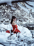 Beautiful woman in red kimono with bare shoulders sitting on snow in a winter nature scenery by a river Image © MaximImages, License at https://www.maximimages.com