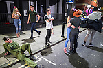 © Joel Goodman - 07973 332324 . 27/12/2016 . Wigan , UK . A man in a Top Gun themed jump suit reclines on the pavement smoking a cigarette next to a man wearing a large prosthetic penis . Revellers in Wigan enjoy Boxing Day drinks and clubbing in Wigan Wallgate . In recent years a tradition has been established in which people go out wearing fancy-dress costumes on Boxing Day night . Photo credit : Joel Goodman