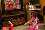 18 month old toddler girl at home watching television, dancing to show