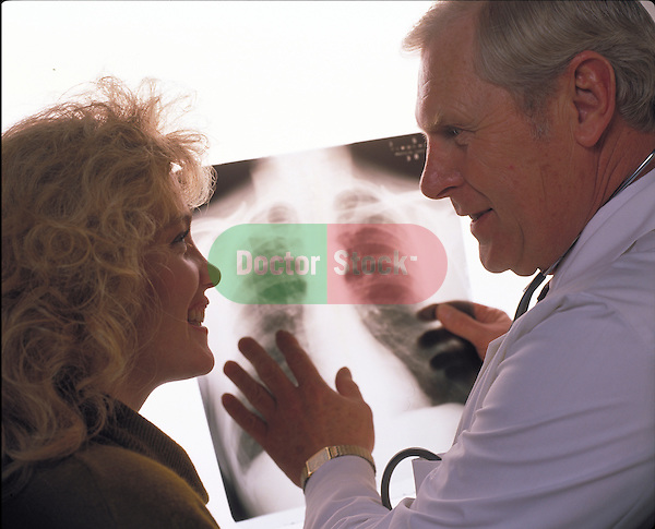 smiling doctor reviewing x-ray with smiling patient