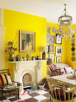 The kitchen/dining area is painted a daffodil yellow and enjoys a Victorian fireplace at one end