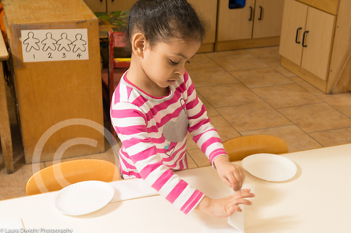 Education Preschool 4 year olds class job setting the table for lunch girl folding napkin