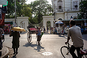 A cyclist rides past a rickshaw puller in front of an entrance to Presidency University on College Street in Kolkata, India, on Friday, May 26, 2017. Photographer: Sanjit Das