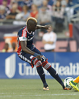 New England Revolution midfielder Saer Sene (39) takes a shot. In a Major League Soccer (MLS) match, Houston Dynamo (orange) defeated the New England Revolution (blue), 2-1, at Gillette Stadium on July 13, 2013.