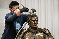 A man works on cleaning up a statue of former President Andrew Jackson in the Rotunda at the U.S. Capitol in Washington, DC, Tuesday, January 12, 2021. Credit: Rod Lamkey / CNP /MediaPunch