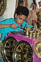 Tunisia, Sidi Bou Said.  Young Boy Tapping Designs into Brass Trays in a Souvenir Shop.