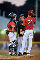 Batavia Muckdogs pitching coach Chad Rhoades (15) talks with pitcher Eli Villalobos (21) and catcher Andres Sthormes (44) during a NY-Penn League game against the State College Spikes on July 3, 2019 at Dwyer Stadium in Batavia, New York.  State College defeated Batavia 6-4.  (Mike Janes/Four Seam Images)