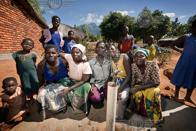 The local water committee gather around the newly installed water tap. ActionAid, along with the local women's group Chigwirizano, constructed a three kilometre long water pipeline providing clean water to Ntalava village and the surrounding area....