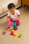 18 month old toddler girl at home sitting on floor making tower of stacking plastic cups