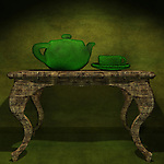 Green teapot with a cup on a table