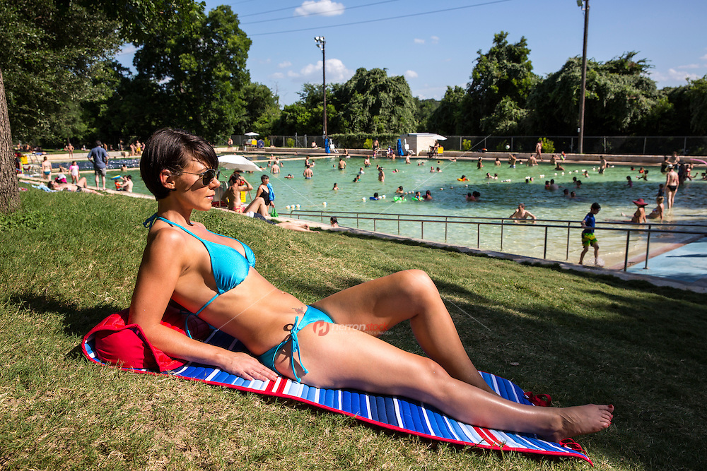Beautiful young woman in bikini laying out and sunbathing at the historic spring fed Deep Eddy Pool in Austin, Texas.