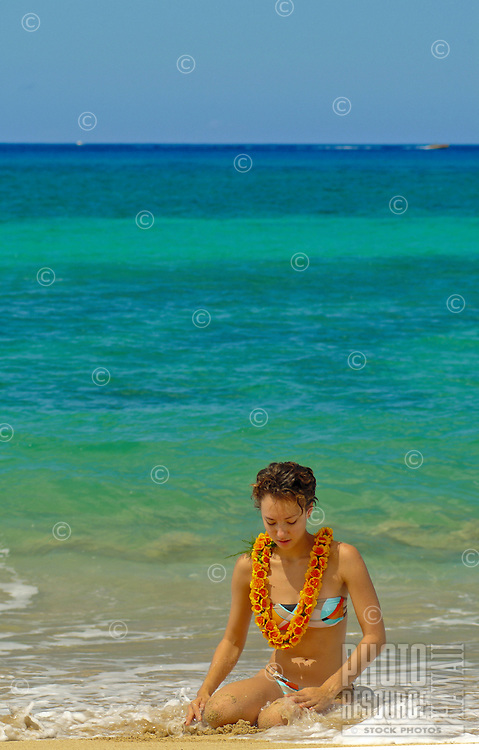 Young woman sitting on the beach with flower lei