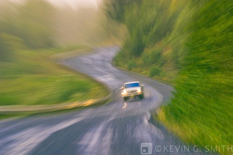 Car on curvey gravel road in the rain, motion blur, fog, fall, Cape Chiniak Road, Kodiak Island, Alaska, USA.