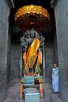 Buddhist faithful by a Buddha statue at Angkor Wat, Cambodia