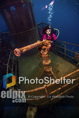 10 June 2014: SCUBA Diver Sally Herschorn discovers a deck mounted gun on the USS Kittiwake, a former United States Navy submarine rescue vessel, off Seven Mile Beach, on the West Shore of Grand Cayman Island. Purchased by the government of the Cayman Islands, the Kittiwake was intentionally sunk on January 5, 2011, to create an artificial reef in the Cayman Marine Park. Located in the British West Indies in the Caribbean, the Cayman Islands are renowned for excellent scuba diving, snorkeling, beaches and banking.  Mandatory Credit: Ed Wolfstein Photo *** RAW (NEF) Image File Available ***