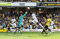 Heurelho Gomes  of Watford punches the ball under pressure from Eder of Swansea   during the Barclays Premier League match Watford and Swansea   played at Vicarage Road Stadium , Watford
