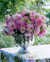 Pink roses and dahlias picked fresh from the garden and arranged in a silver vase