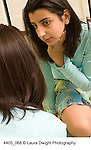 teenage girl 12 years old in bedroom looking at self in mirror vertical