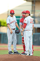 Greeneville Reds pitching coach Chad Cordero (32) has a meeting on the mound with starting pitcher Lyon Richardson (16) and catcher Hunter Oliver (28) during the game against the Pulaski Yankees at Calfee Park on June 23, 2018 in Pulaski, Virginia. The Reds defeated the Yankees 6-5.  (Brian Westerholt/Four Seam Images)