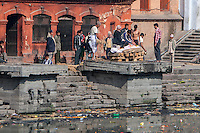 Nepal, Pashupatinath.  Cremation Stages.  With the Corpse Wrapped in a Sheet, Family Members Prepare to Light the Fire.
